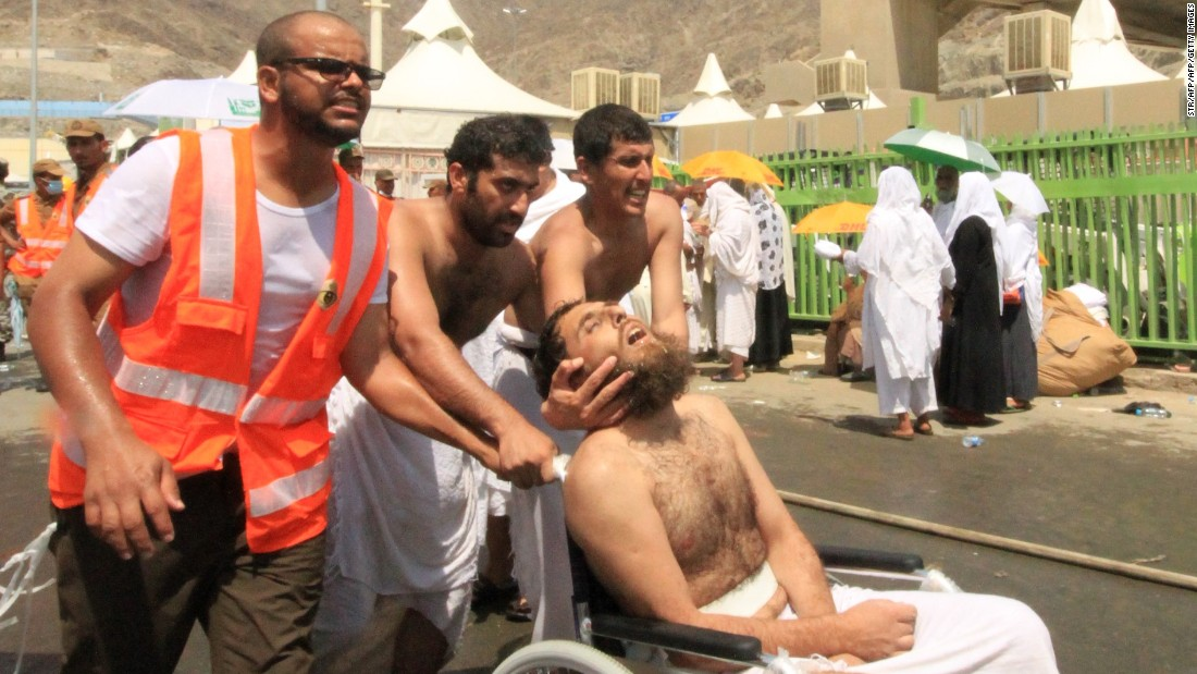 Saudi emergency personnel and Hajj pilgrims push a wounded person in a wheelchair at the site of a stampede in Mina on Thursday, September 24, 2015.