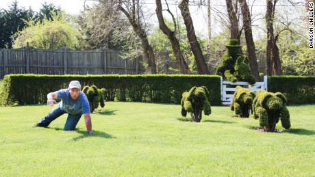 Mike Rowe crawls along with some dogs at Ladew Topiary Gardens.