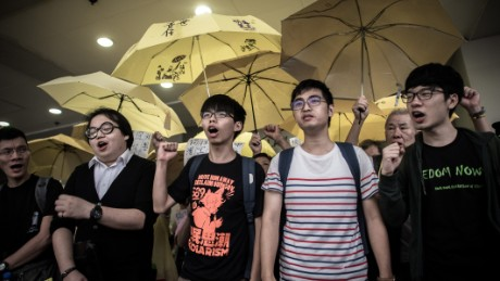 Student protesters Joshua Wong (C), Alex Show (2nd L) and Nathan Law (R) shout slogans outside a court of justice in Hong Kong on September 2, 2015. The students appeared in court for their participation in the 2014 pro-democracy Occupy movement. AFP PHOTO / Philippe Lopez        (Photo credit should read PHILIPPE LOPEZ/AFP/Getty Images)
