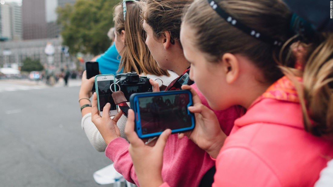 People eagerly prepare their phones to capture imagery as they wait for the Pope to pass by.