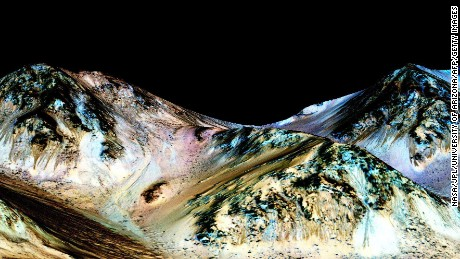 """A handout image made available by NASA on September 27, 2015, shows dark, narrow, 100 meter-long streaks called recurring slope lineae flowing downhill on Mars, inferred to have been formed by contemporary flowing water. Recently, planetary scientists detected hydrated salts on these slopes at Hale crater, corroborating their original hypothesis that the streaks are indeed formed by liquid water. The blue color seen upslope of the dark streaks are thought not to be related to their formation, but instead are from the presence of the mineral pyroxene. AFP PHOTO /NASA/JPL/UNIVERSITY OF ARIZONA ==RESTRICTED TO EDITORIAL USE - MANDATORY CREDIT """"AFP PHOTO /NASA/JPL/UNIVERSITY OF ARIZONA"""" - NO MARKETING NO ADVERTISING CAMPAIGNS - DISTRIBUTED AS A SERVICE TO CLIENT - AFP IS NOT RESPONSIBLE FOR ANY DIGITAL ALTERATIONS TO THE PICTURE'S EDITORIAL CONTENT, DATE AND LOCATION ==-/AFP/Getty Images"""