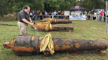 """In this photo provided by the University of South Carolina, University of South Carolina archaeologist and state archaeologist Jon Leader washes and inspects one of the three Civil War cannons pulled from the Pee Dee River on Tuesday, Sept. 29, 2015, in Mars Bluff, S.C. The three cannons were dumped in the river by Confederate forces from the gunboat CSS Pee Dee in 1865 in order to keep them from falling into the hands of Union forces. (Margaret """"Peggy"""" Ryan Binette/University of South Carolina via AP)"""