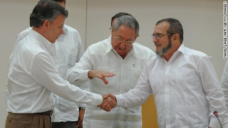 """Colombian President Juan Manuel Santos (L) and the head of the FARC guerrilla Timoleon Jimenez, aka Timochenko (R), shake hands in front of Cuban President Raul Castro (C) during a meeting in Havana on September 23, 2015. The Colombian government and FARC rebels announced a key breakthrough in their nearly three-year peace talks Wednesday with the signing of a deal on justice for crimes committed during the five-decade conflict. The deal includes the creation of special courts and a broad amnesty, though this will not cover """"crimes against humanity, serious war crimes"""" and other offenses including kidnappings, extrajudicial executions and sexual abuse, said officials from Cuba and Norway, the guarantors in the talks. AFP PHOTO / YAMIL LAGE        (Photo credit should read YAMIL LAGE/AFP/Getty Images)"""