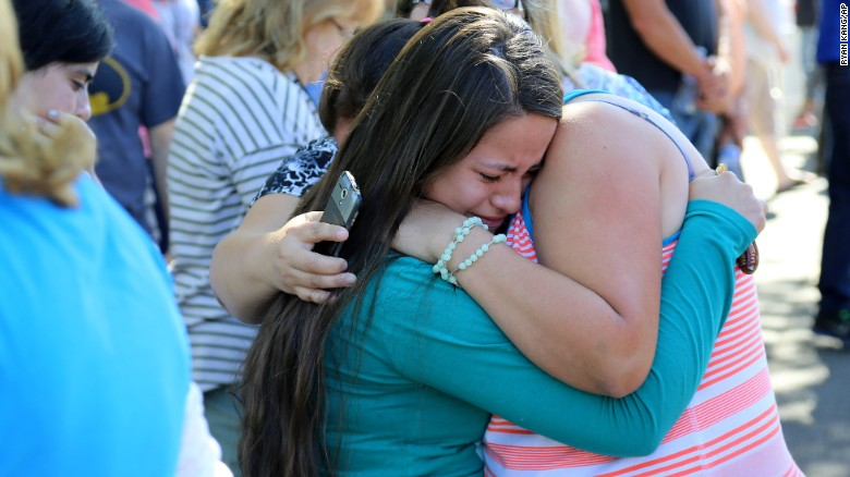 A woman is comforted at the fairgrounds on October 1.