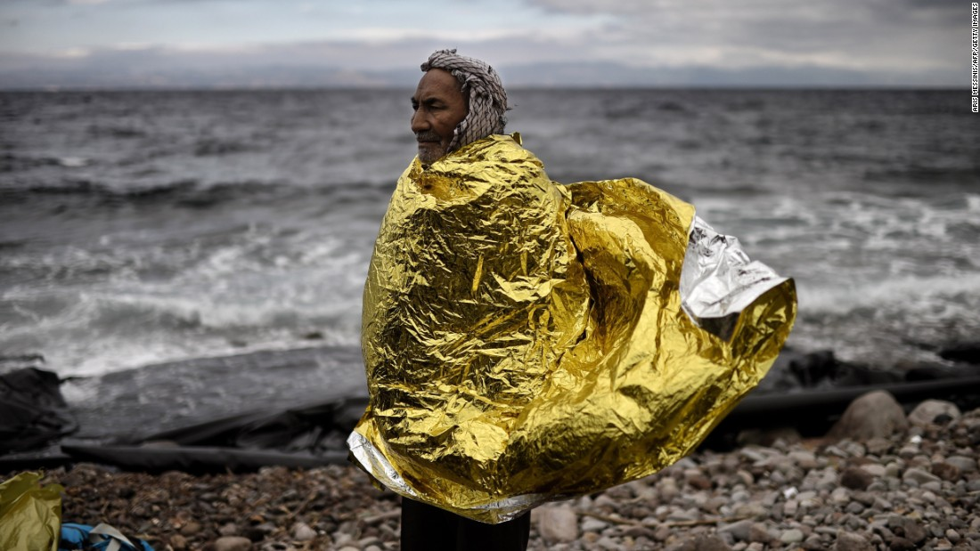 A man wearing a protective blanket stands on the shore of Lesbos, Greece, as refugees and migrants arrive after crossing the Aegean Sea from Turkey on Wednesday, September 30. More than 300,000 refugees and migrants heading to Europe have crossed the Mediterranean Sea so far in 2015, a U.N. spokeswoman says. Click through to see images from the refugee crisis in Europe.