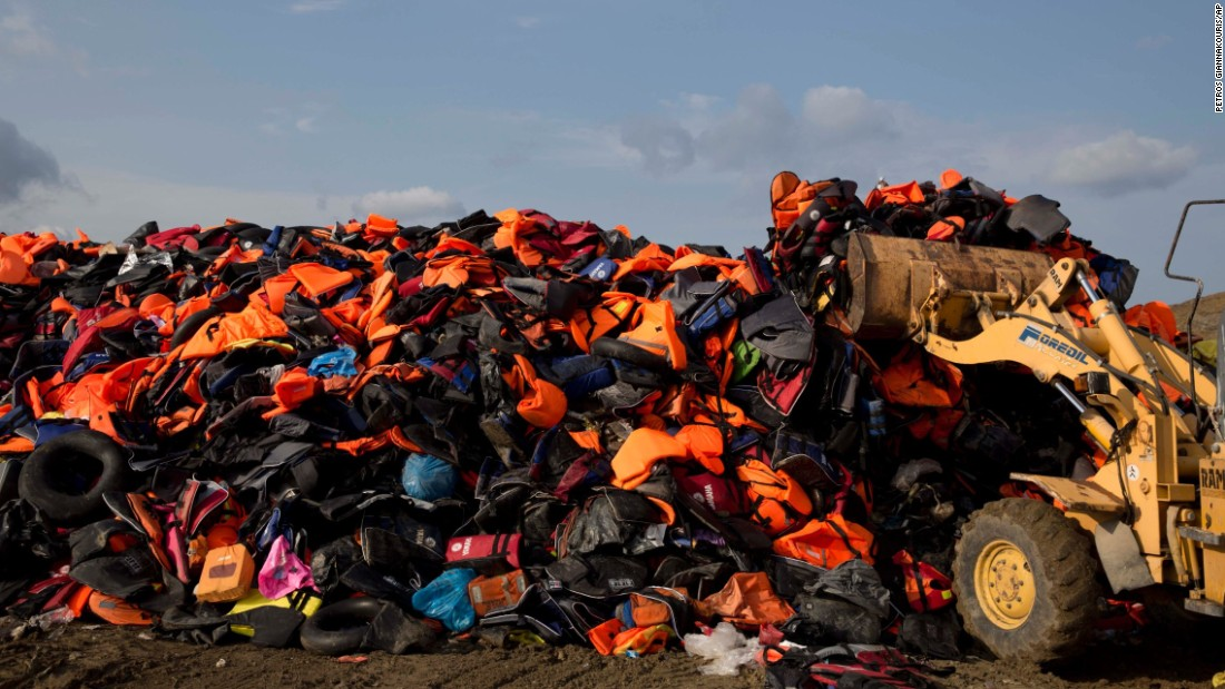 An excavator dumps life vests previously used by migrants at a local dump on the island of Lesbos, Greece, on Thursday, September 24.