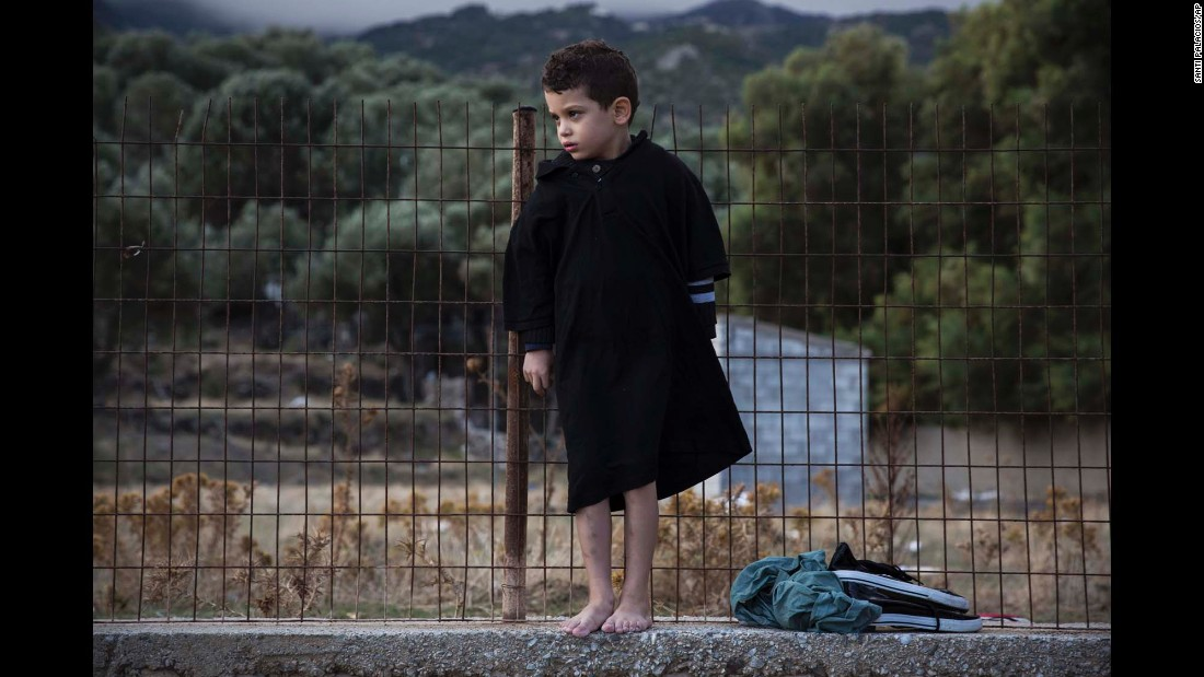 A barefoot boy stands on a concrete wall after his family's arrival at Lesbos, Greece, on Wednesday, September 30.