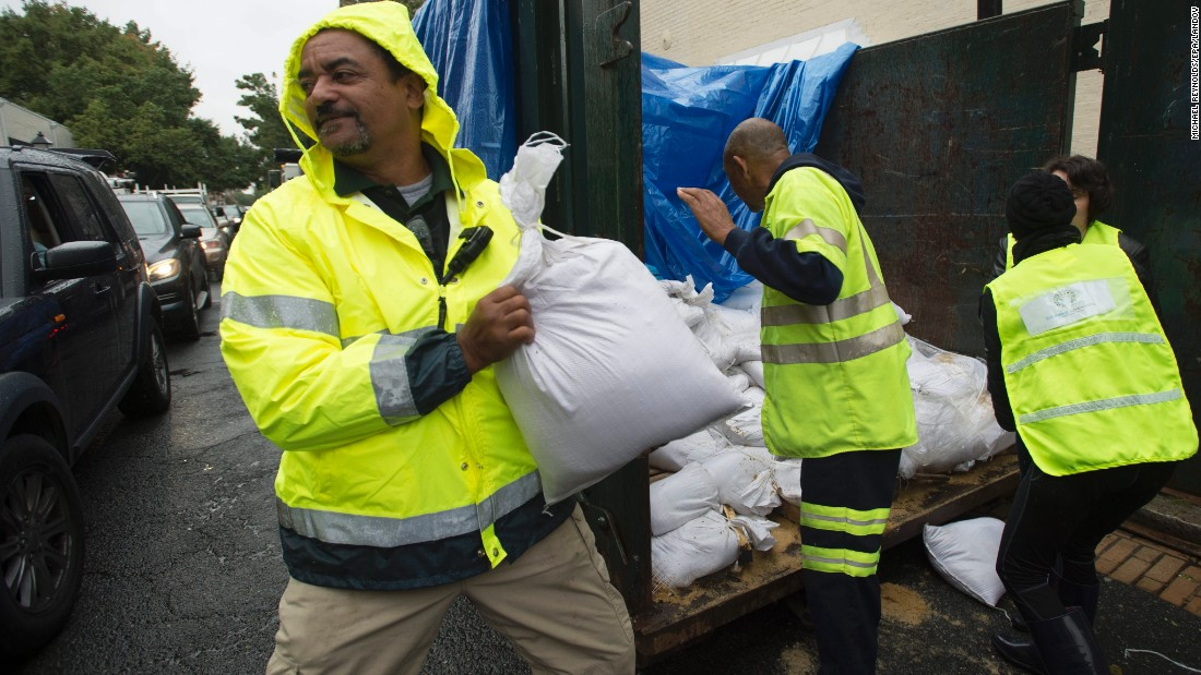 Volunteers and public works employees load sandbags into people's cars on Friday, October 2, as residents of Alexandria, Virginia, prepare for potential flooding.