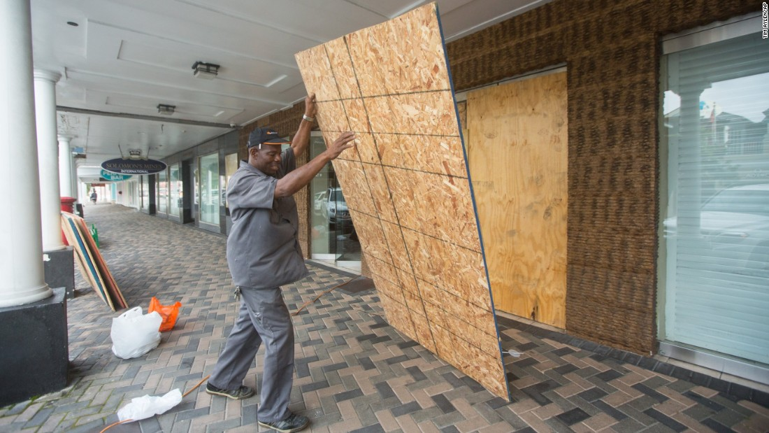 A man in Nassau puts up plywood shutters to cover store windows on Thursday, October 1.