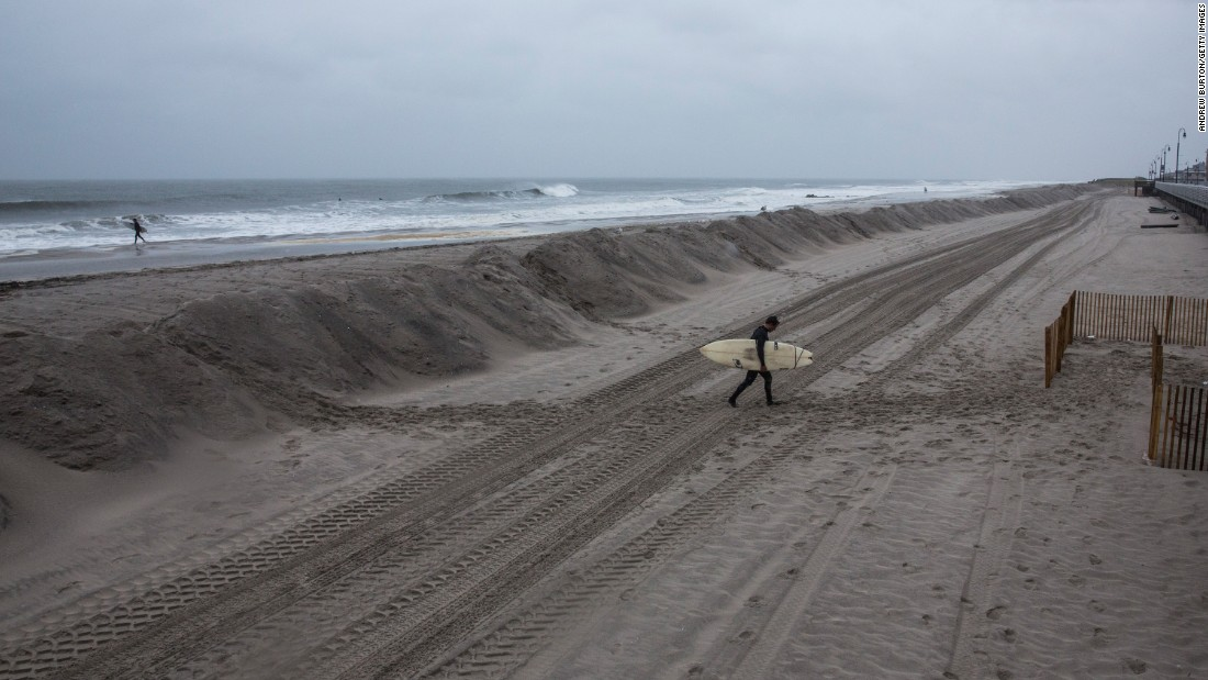 Darren Gallo walks home in Long Beach, New York, after two hours of surfing on October 2. The storm might stay in the Atlantic Ocean, away from the U.S. East Coast, but there is still a concern about heavy rain and potential flooding.