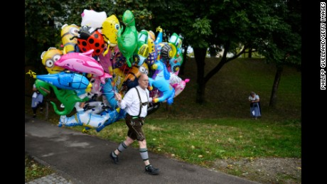 MUNICH, GERMANY - SEPTEMBER 19: A baloon-vendor in bavarian folk attire carries a bunch of helium baloons on the opening day of the 2015 Oktoberfest on September 19, 2015 in Munich, Germany. The 182nd Oktoberfest will be open to the public from September 19 through October 4 and will draw millions of visitors from across the globe in the world's largest beer fest. (Photo by Philipp Guelland/Getty Images)