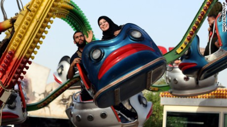 Iraqis enjoy a ride at Amusement City fairgrounds during Eid al-Adha celebrations in Baghdad, Iraq, Friday, Sept. 25, 2015. Eid al-Adha, or Feast of Sacrifice, commemorates what Muslims believe was Prophet Abraham's willingness to sacrifice his son. It is a festive holiday where it is traditional for men, women and children to dress in new clothing and spend time with their families outdoors. (AP Photo/Hadi Mizban)