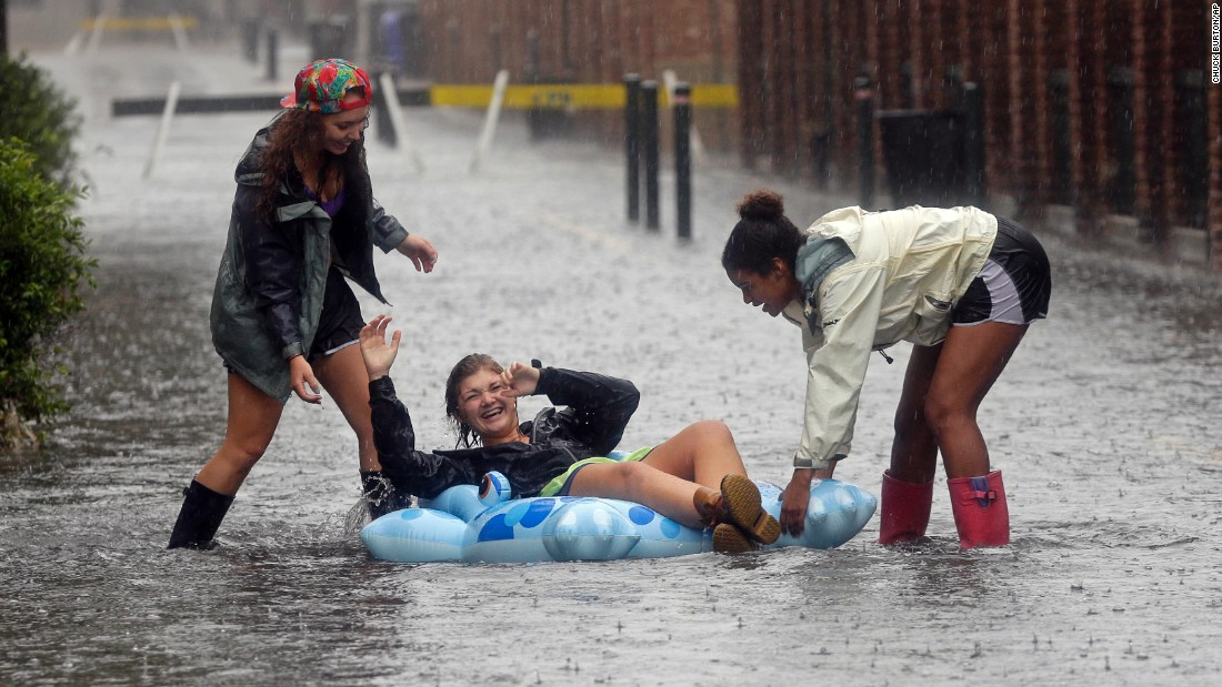 Anna Wilson, center, laughs as she plays with friends Madi Kois, left, and Wesli Jones on a flooded street in Charleston, South Carolina, on October 3.