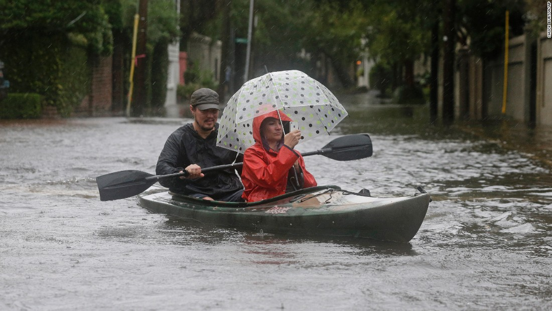 Paul Banker paddles a kayak as his wife Wink Banker takes photos on a flooded street in Charleston, South Carolina, on October 3.