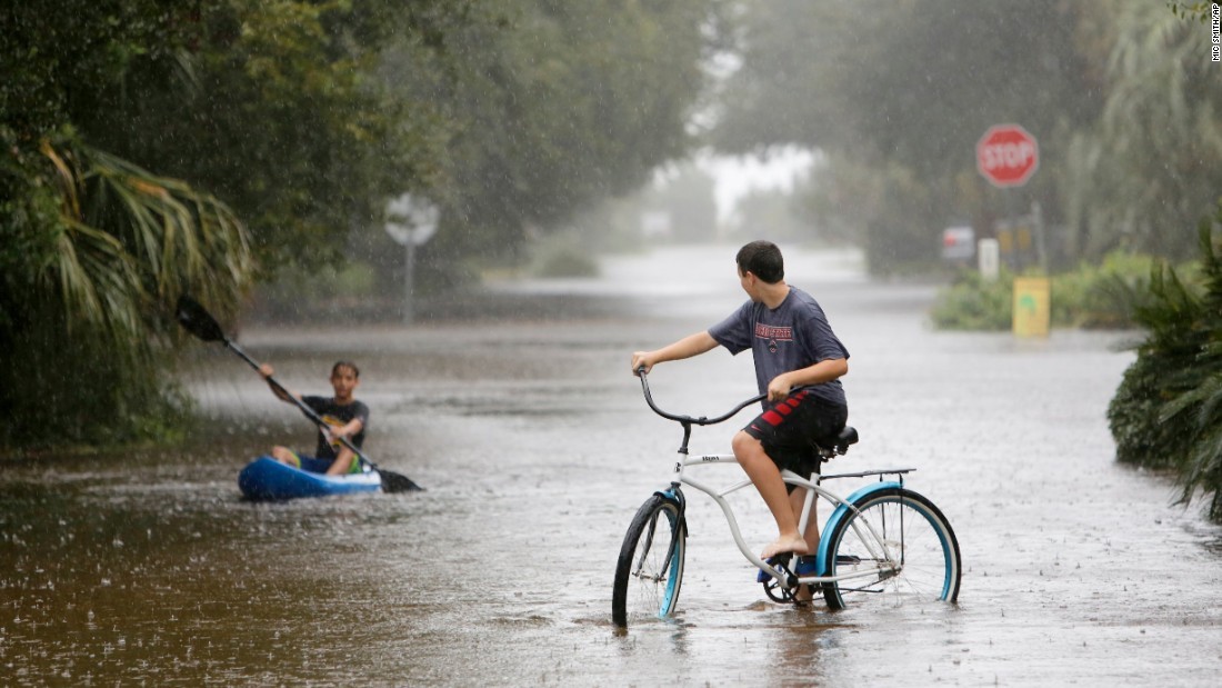 Will Cunningham, 14, rides his bike down Station 29 on Sullivan's Island, South Carolina, ahead of his paddling  friend Patrick Kelly, 14,  on Saturday, October 3.