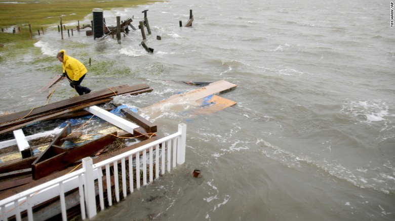 Stuart Tait ties together wood after his house collapsed into the inlet on the Grassy Sound during high tide on Saturday October 3, 2015, north of North Wildwood, New Jersey.