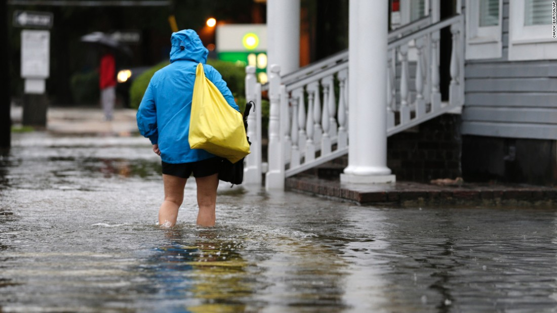 A woman walks down a flooded sidewalk toward an open convenience store in Charleston, South Carolina, on Sunday, October 4.