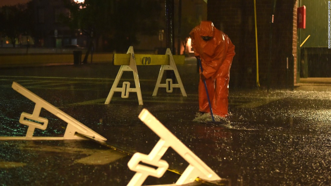 A worker cleans a drain on a flooded street in downtown Charleston, South Carolina, on Saturday, October 3.