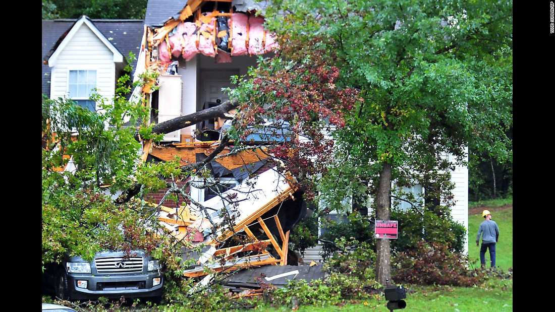 A utility worker examines the damage to a home Charlotte, North Carolina, on October 3.