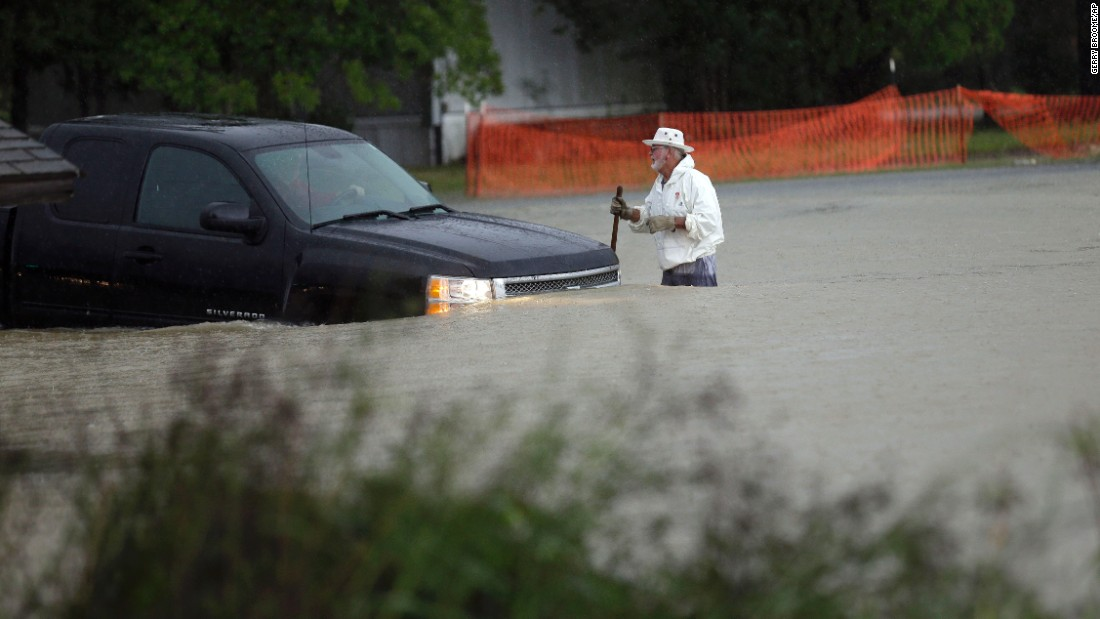 A man watches as a vehicle tries to navigate flood waters in Florence, South Carolina, on October 4.
