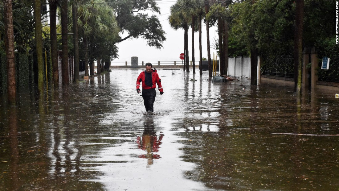 A firefighter walks down a flooded street in downtown Charleston, South Carolina, on October 4.