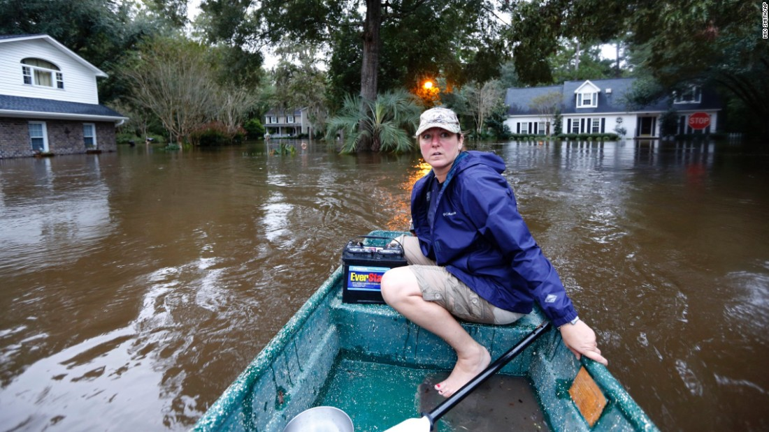 A woman uses her boat to check on neighbors and see if they want to evacuate in Summerville, South Carolina, on Monday, October 5.