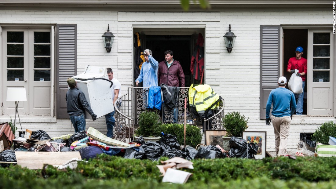 Neighbors and friends help clean up a home affected by flooding in Columbia on October 5.