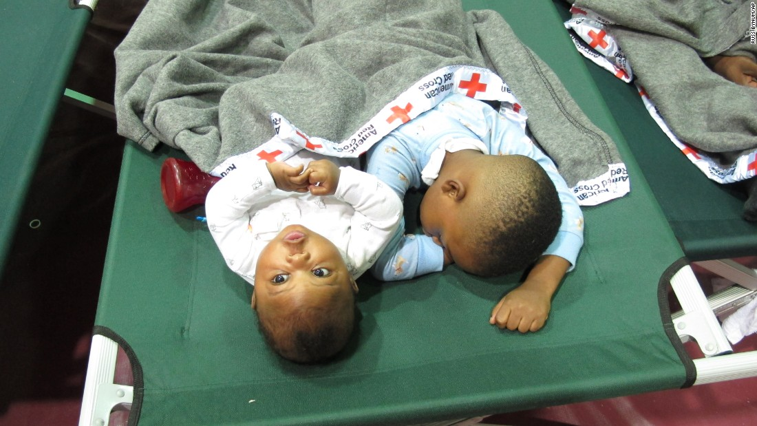 Five-month-old Jeremiah Odum, left, and his 2-year-old brother, Braxton Odum, nap on a cot in a high school gymnasium being used as a Red Cross shelter for flood evacuees in Rowesville, South Carolina, on October 5.