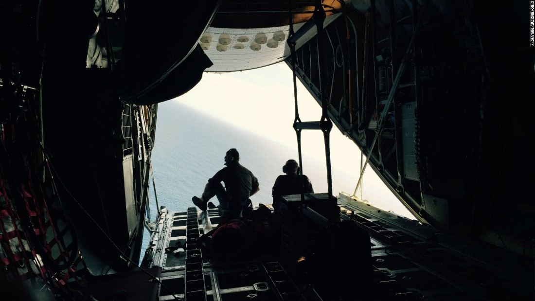 """The plane makes a sharp bank to """"orbit,"""" or fly back over, a piece of debris that the crew wants to check. On the second pass, the cockpit crew gives it another look, as will the crewmember operating the onboard camera. Here, Petty Officers 3rd Class Chris LaBelle, left, and Mark Strock sit on the edge of the cargo door in hopes of getting a better perspective on the debris."""