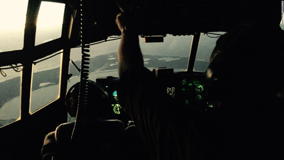 When the HC-130 first took off, the cockpit was dark, the instruments on the control panel offering the only light. Here, the first rays of sun gleam into the cockpit as Lt. Janelle Setta, a copilot, left, and Fielder, the engineer, guide the plane to the search area.
