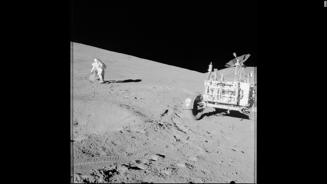 Scott studies a boulder on the moon during Apollo 15.