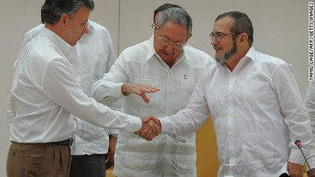 "Colombian President Juan Manuel Santos (L) and the head of the FARC guerrilla Timoleon Jimenez, aka Timochenko (R), shake hands in front of Cuban President Raul Castro (C) during a meeting in Havana on September 23, 2015. The Colombian government and FARC rebels announced a key breakthrough in their nearly three-year peace talks Wednesday with the signing of a deal on justice for crimes committed during the five-decade conflict. The deal includes the creation of special courts and a broad amnesty, though this will not cover ""crimes against humanity, serious war crimes"" and other offenses including kidnappings, extrajudicial executions and sexual abuse, said officials from Cuba and Norway, the guarantors in the talks. AFP PHOTO / YAMIL LAGE        (Photo credit should read YAMIL LAGE/AFP/Getty Images)"