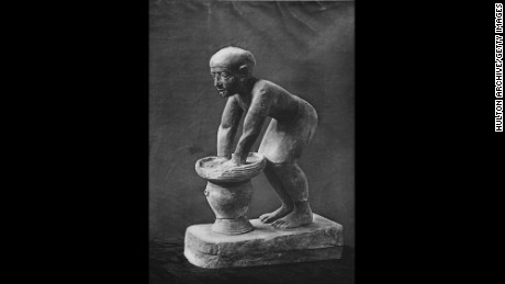 A limestone statuette of an Egyptian servant pressing out the fermented barley-bread from which beer was brewed, circa 1930. He pushes the bread through a basket and beer drips into a large pot with a spout below. The statuette was found at Saqqara, the necropolis of the ancient Egyptian city of Memphis. (Photo by Hulton Archive/Getty Images)