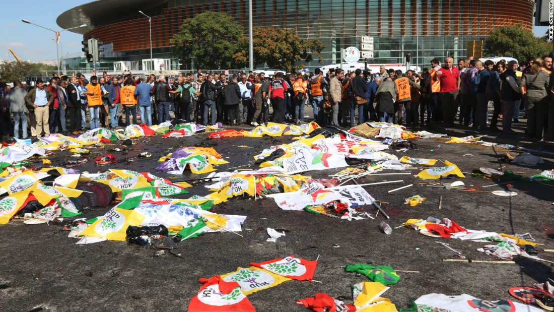 People surround the area where bodies of victims are covered with flags and banners.