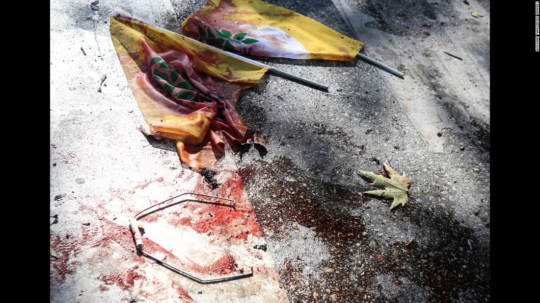 Bloodstained flags lie on the ground at the site of the explosion.