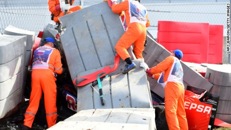 Marshalls remove barriers from the top of the Toro Rosso of Carlos Sainz Jr after the Spaniard's high speed crash at the Russian Grand Prix.