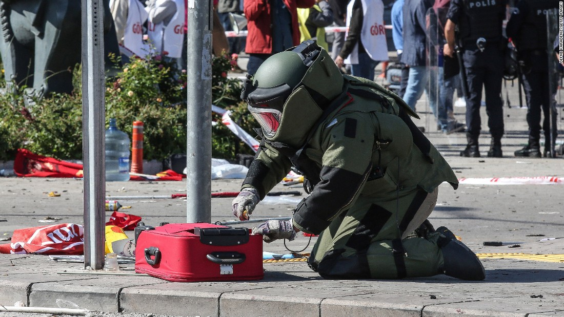 A bomb expert investigates a suitcase at the blast scene.