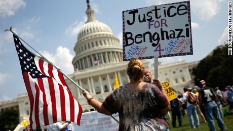 """WASHINGTON, DC - SEPTEMBER 11:  Jennifer Brandt holds signs during a """"Call to Action"""" rally held by various conservative organizations on the grounds of the U.S. Capitol, marking the one year anniversary of the attacks on the U.S. compound in Benghazi September 11, 2013 in Washington, DC. U.S. Ambassador Chris Stevens, Sean Smith, Glen Doherty and Tyrone Woods were all killed during the attacks last year."""
