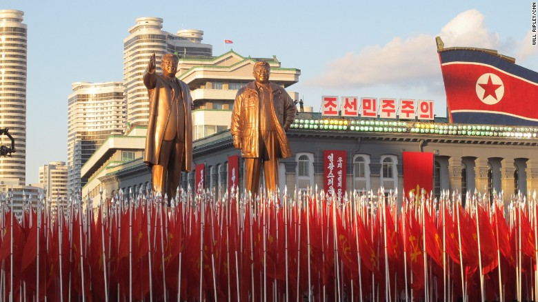 North Korean soldiers march below statues of North Korea's founding president Kim Il Sung and his son Kim Jong Il.