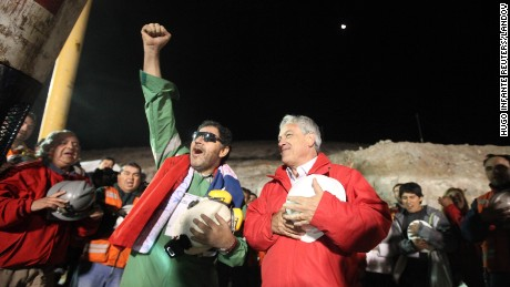 Trapped miner Luis Urzua raises his arm as he stands with Chile's President Sebastian Pinera after reaching the surface to become the last to be rescued from the San Jose mine in Copiapo on October 13, 2010.