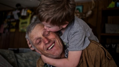 """Skylor Cox, 3, jumps on his father's back to give him """"little kissies"""" at their home in Fordsville, Ky., on February 15, 2014.""""You've gotta be close with your little ones. When your kids get grown you lose them. You lose that certain part of them,"""" Faron said."""