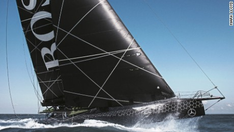 Hugo Boss arcs through the water with Alex Thomson at the helm under blue skies