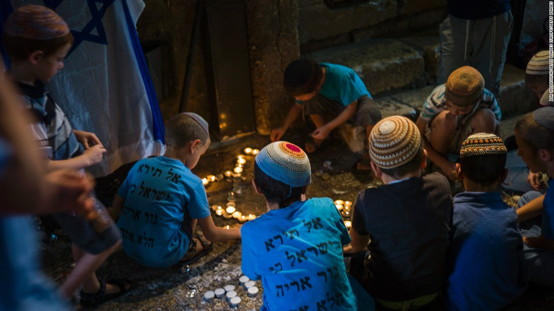 Jewish children pray at the site of a stabbing attack in the Muslim Quarter of Jerusalem's Old City on Monday, October 12.