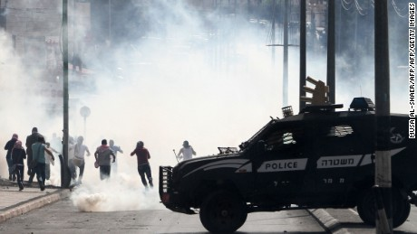 An Israeli police vehicle drives in front of Palestinian protesters running away during clashes on October 13, 2015 in the West Bank city of Bethlehem. A Palestinian was killed in the clashes, Palestinian medical sources said, the latest such incident in nearly two weeks of violence.     AFP PHOTO/ MUSA AL-SHAER        (Photo credit should read MUSA AL-SHAER/AFP/Getty Images)