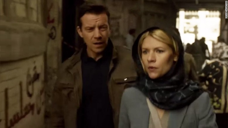 "Claire Danes star of hit U.S. TV series ""Homeland"" walks past graffiti on a wall that says in Arabic: ""Homeland is NOT a series."""