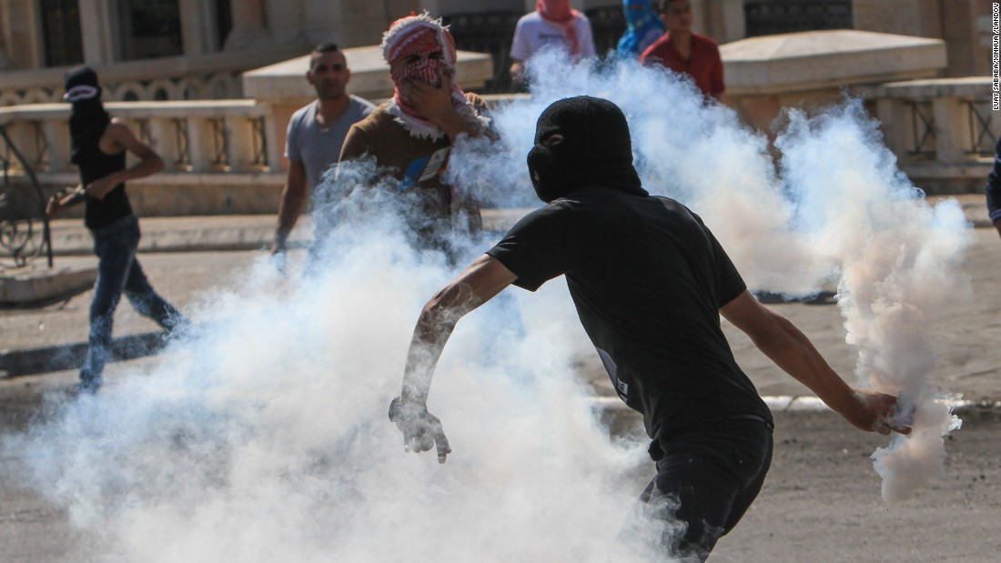 A Palestinian protester throws a tear-gas canister back toward Israeli soldiers during clashes in the West Bank city of Bethlehem on Thursday, October 15.
