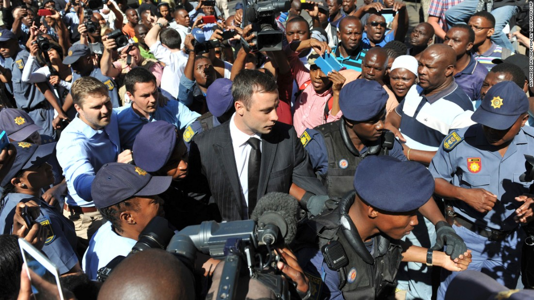 Oscar Pistorius, wearing the black tie, arrives outside a courtroom in Pretoria, South Africa, on October 21, 2014.