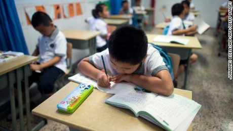 Seven year old Wei Yueran (L), who also has the English name Harney, attends a Chinese class at the Jinqao Center Primary School in Shanghai on September 1, 2014. After spending one year in the US, Yueran has joined the second class of the Jinqao Center Primary School in Shanghai's Pudong district. The Shanghai Education Commission recently announced the opening of 50 new public schools in the city, according to local news.   AFP PHOTO / JOHANNES EISELE        (Photo credit should read JOHANNES EISELE/AFP/Getty Images)