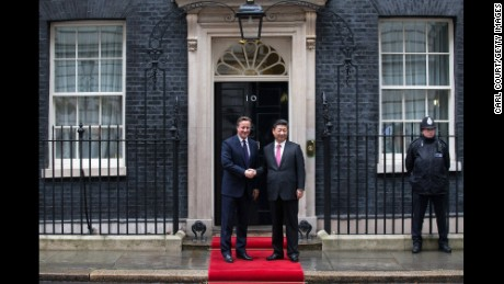 Britain's Prime Minister David Cameron greets Xi as he arrives at 10 Downing Street.