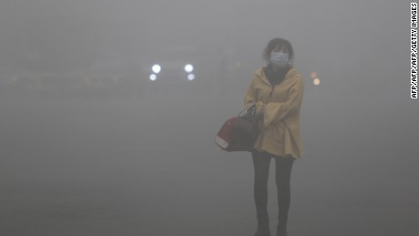 A woman wearing any deal with mask walks within hefty smog throughout Harbin, northeast China's Heilongjiang province, upon October 21, 2013. Korean soldier examines S.   CHINA OUT     AFP PHOTO        (Photo credit score should study STR/AFP/Getty Images)